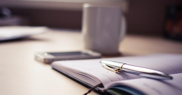 使いかけのペンとノートとマグカップ