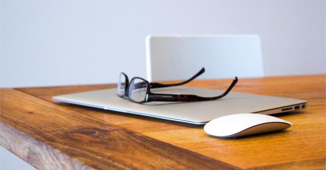 机の上のノートPCとメガネ