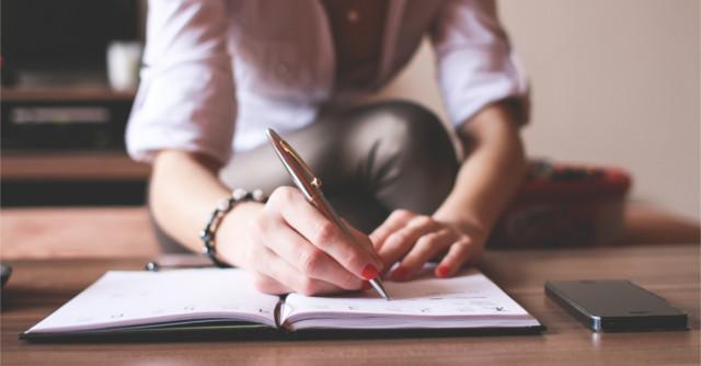 テーブルで上でノートに書き込みをする女性